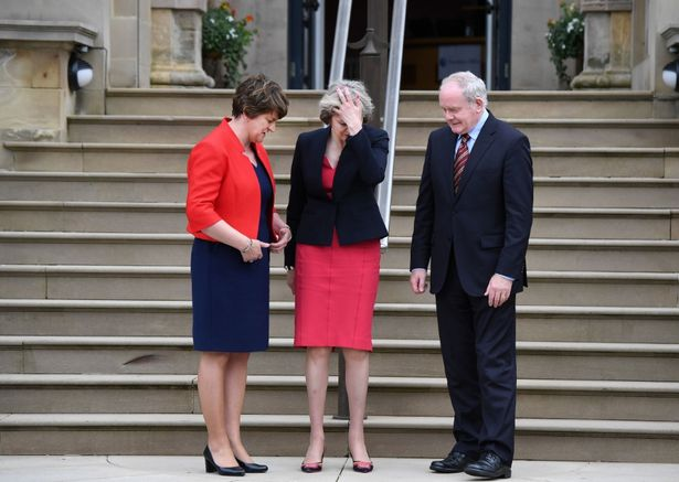 Theresa May facepalming whilst stood between current first minister Arlene Foster and former deputy first minister the late Martin McGuinness last year. Credit: Charles McQuillan/Getty Images