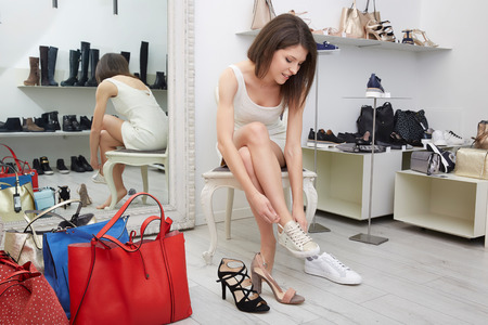 74443358_S_Shoes_shopping_trying_on_fitting_woman_high_heals_sneakers_legs_feet.jpg