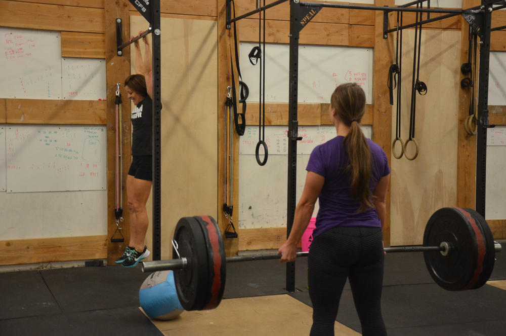 Rachel finishing uper her deadlifts while Ang hangs on.