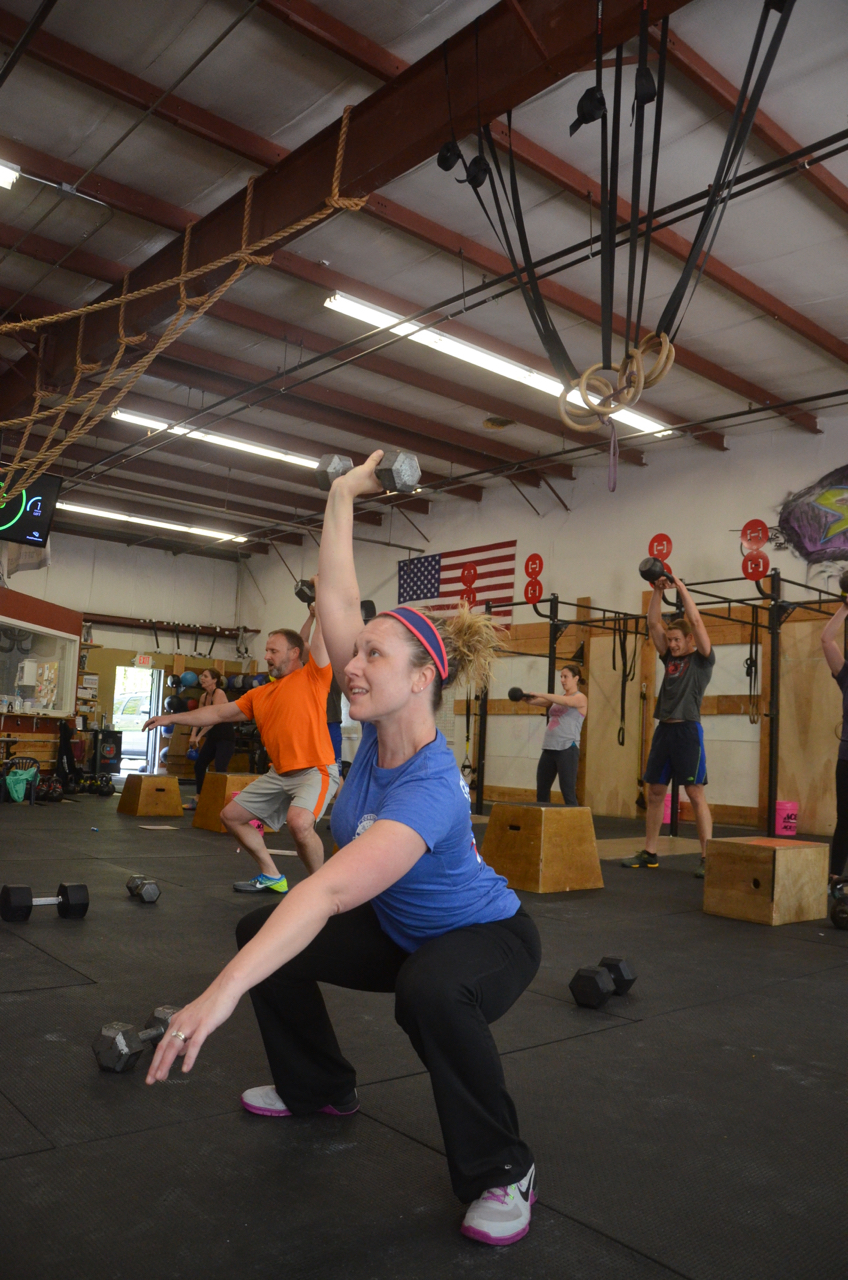Stacy at the bottom of her dumbbell overhead squats.