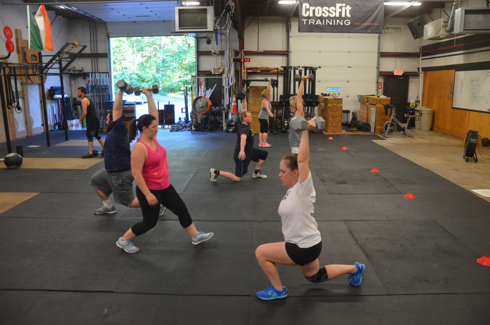 The 6pm class during their 20' overhead walking dumbbell lunge.