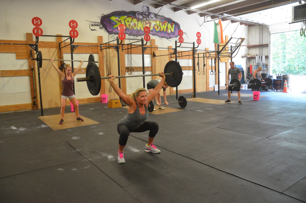 Kristie and the 9:30 class working up their Overhead Squat & Toes to Bar ladder.