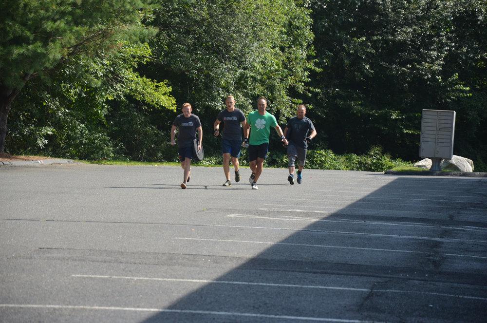 Team Chris, Tanner, Funk, Matt carrying their bar & weights.
