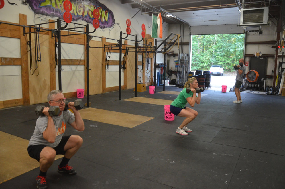 Dave and Hope during their 15-12-9 of dumbbell clusters and pull-ups.