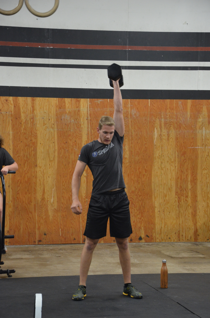 Tanner showing a solid lock out on the dumbbell snatch.