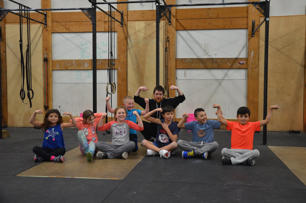 Coach Mikey and the Strongtown  Kids flexing after a strong week!