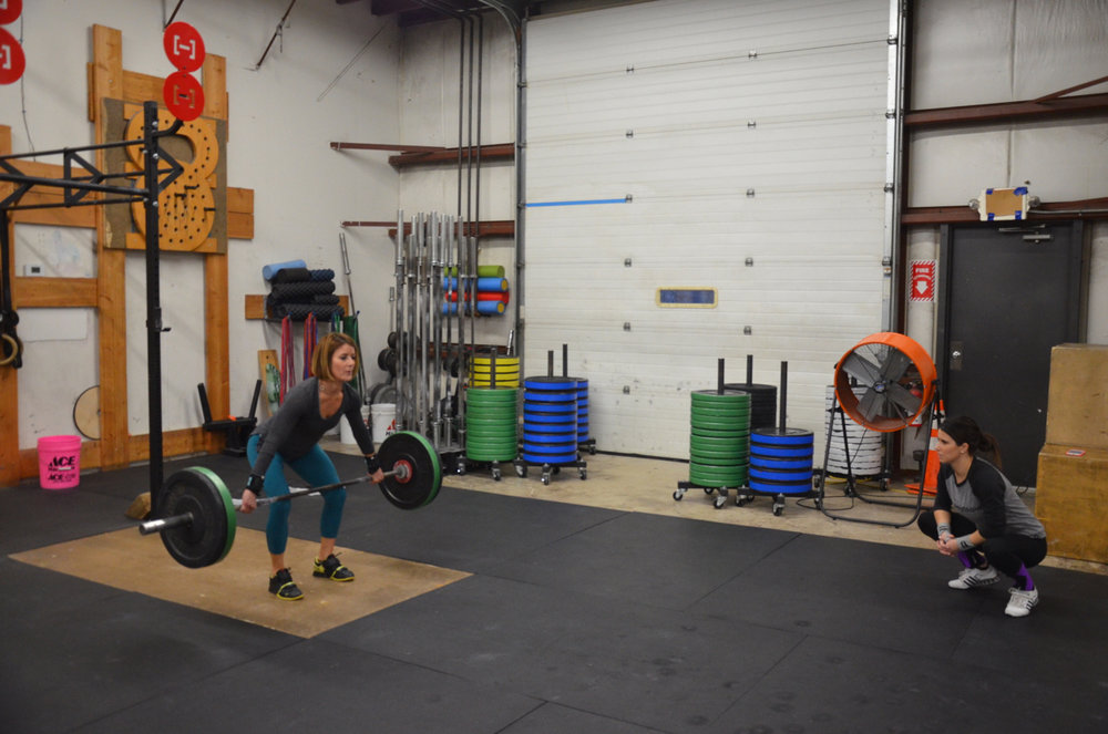 Jen making sure Angela stay tight during the Snatch Grip Deadlift.
