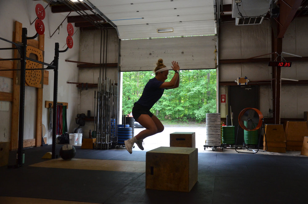Hailey mid air on her box jumps at Saturday's 10am class.
