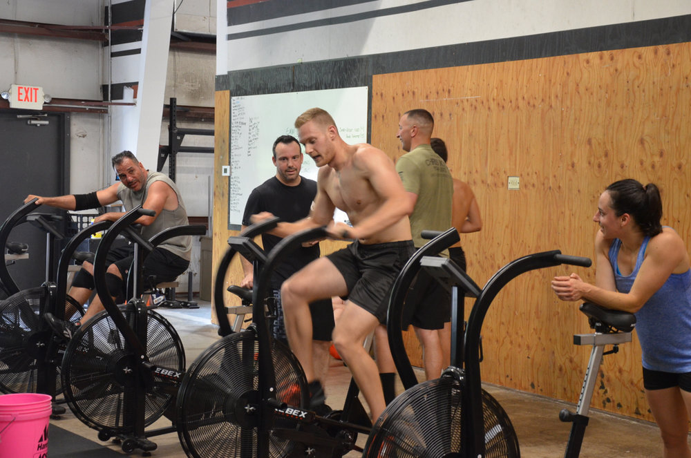 Tanner getting cheered on by Kate, Tommy and Rob while he goes for the high score on Death by Bike Calories.