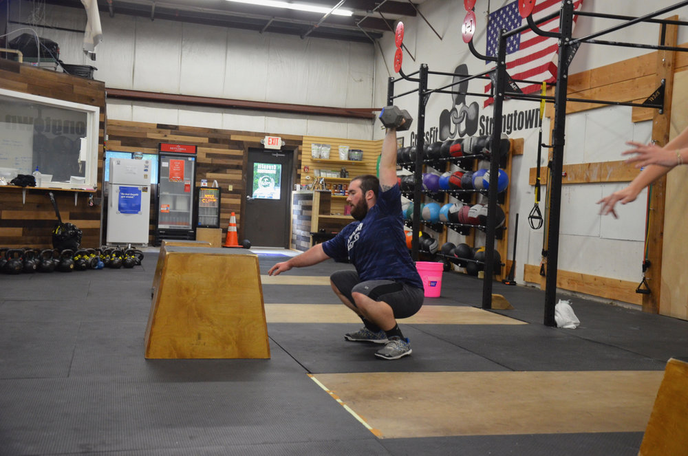 Zach showing great form on his single arm dumbbell overhead squats.