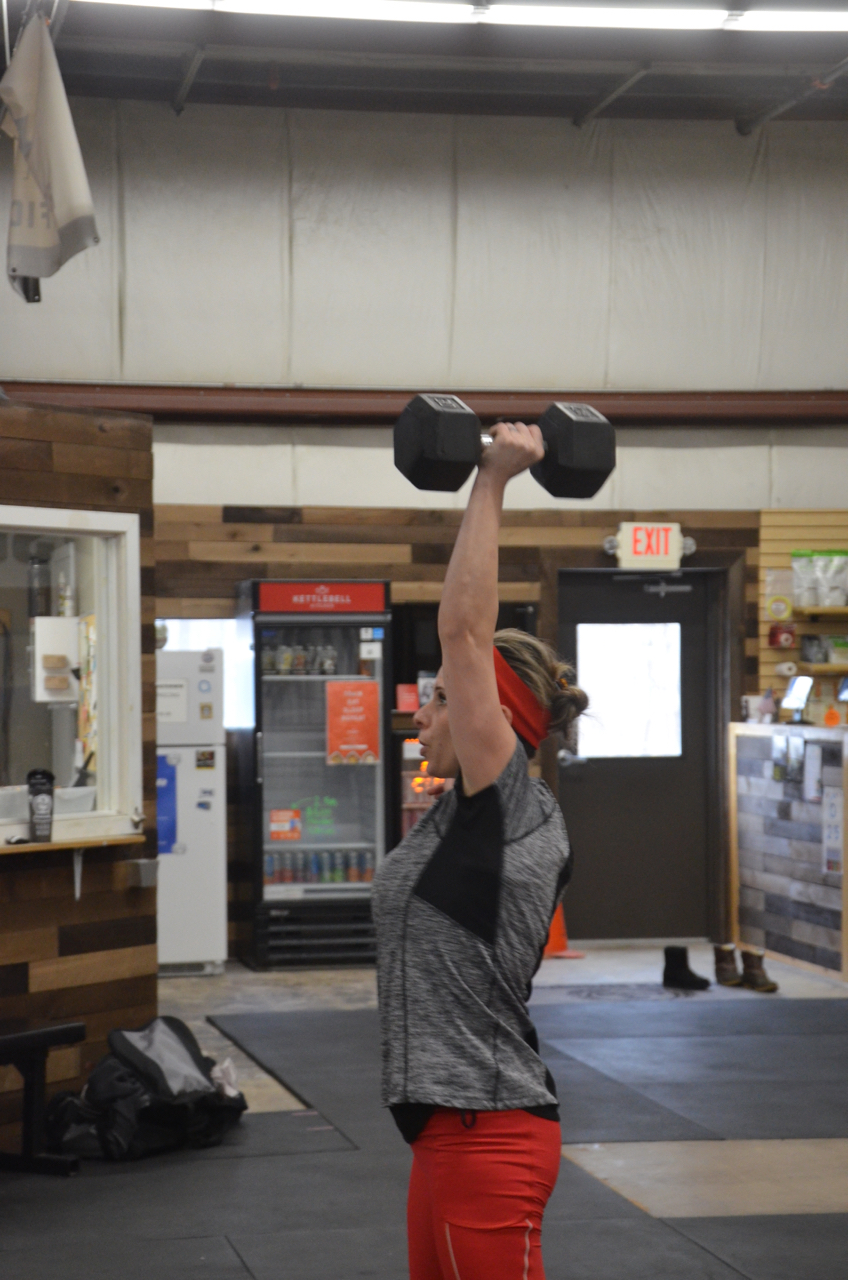 Sabrina staying focused on her dumbbell hang clean and jerk.