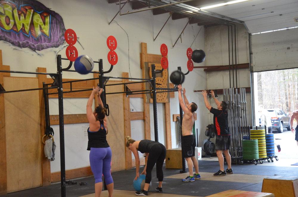 Rachie, Britt, Dan and Truck working through 30 wall-ball.