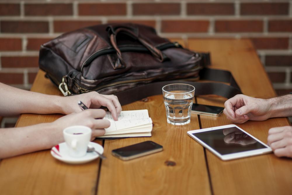 Tafel met koffie, iPad, tafereel van een meeting