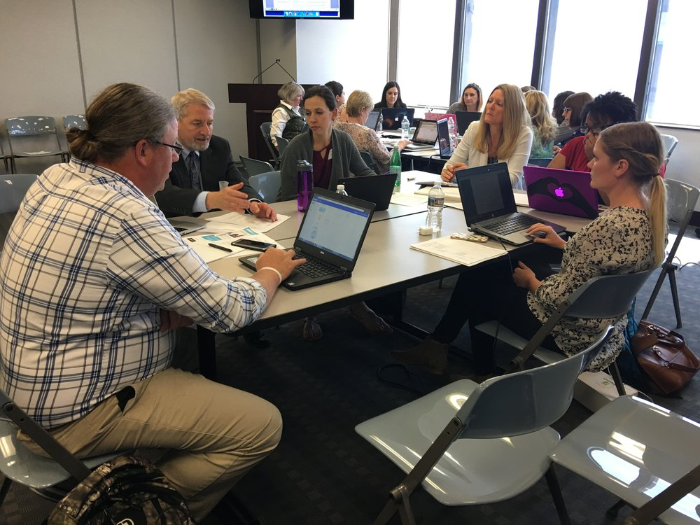 Teachers from various school districts work on an Algebra I OER textbook.
