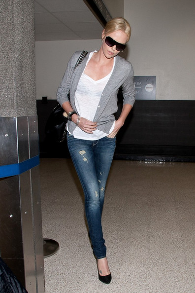 Charlize Theron uses a v-neck to de-emphasize her large chest while wearing a long skinny jean (stylebistro.com).