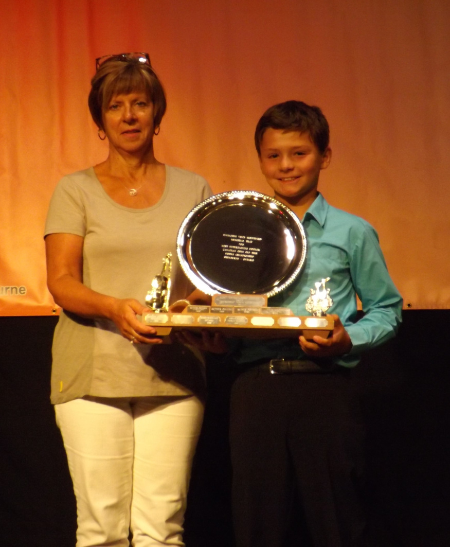 Lucas Candelino of Barrie, ON (right) winner of the 9 & Under Class and the Invincible Vince Mountford Memorial Trophy for Most Entertaining Fiddle with Contest Chair Sandra Gallaugher.