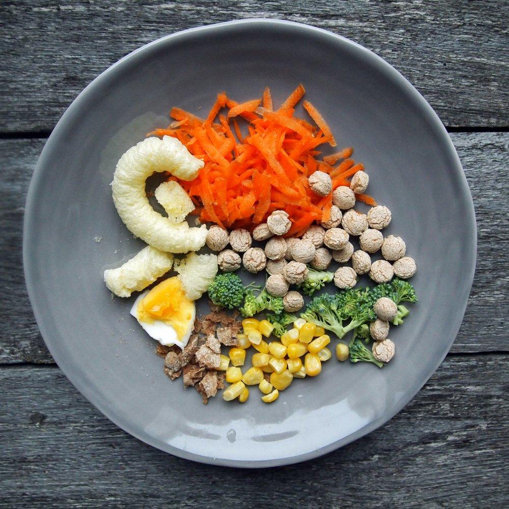 Porkkanaraastetta, talkmuruja, parsakaalia, maissia, näkkileipää, keitettyä kananmunaa ja maissinaksuja.