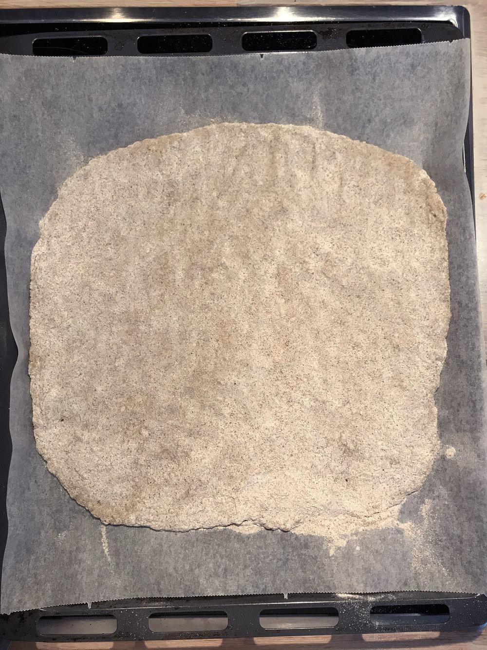 Taikina leivitetään pellille ja päälle ripotellaan jauhoja. Lopuksi se taputellaan litteäksi käsin.