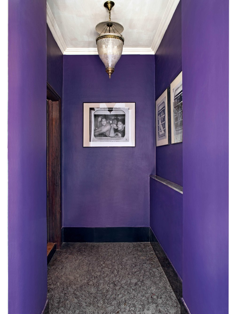 The entryway has aubergine-coloured walls adorned with photographs depicting travellers in a three-tier sleeper train. A traditional lamp hangs from the ceiling.