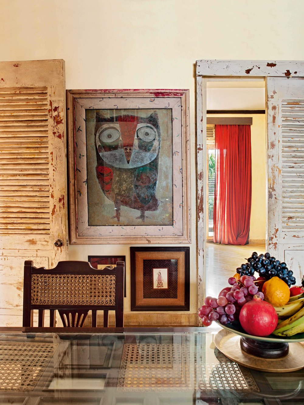 The small dining room features art from the Sabyasachi Art Foundation and works by Dhruvi Acharya. The dining table is made from wood, rattan and glass from Kochi.