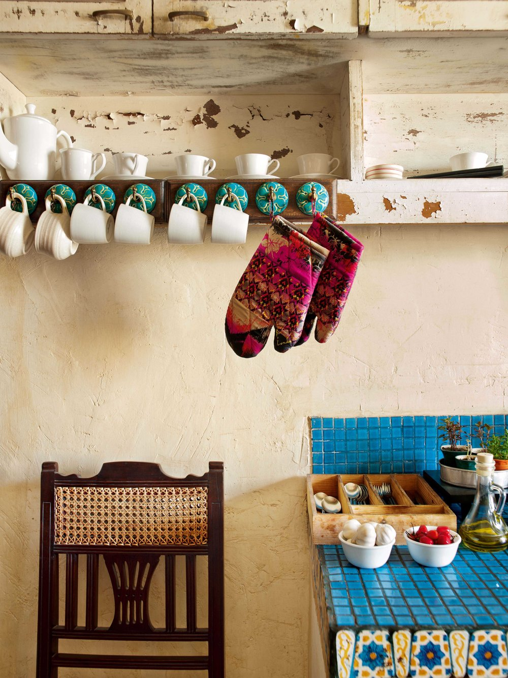 White porcelain, distressed wood cabinets and ethnic tiles are a feature of the open kitchen.