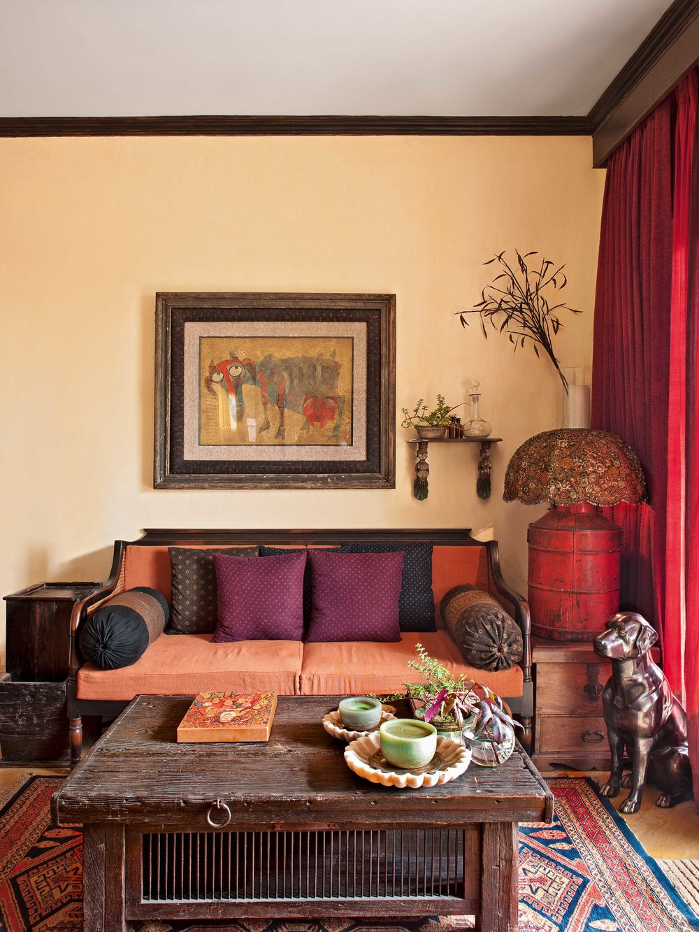 corner of Mukherjee's living room has antique textiles,eclectic art and old rugs. A brass dog and a tin barrel lamp are quirky accents.