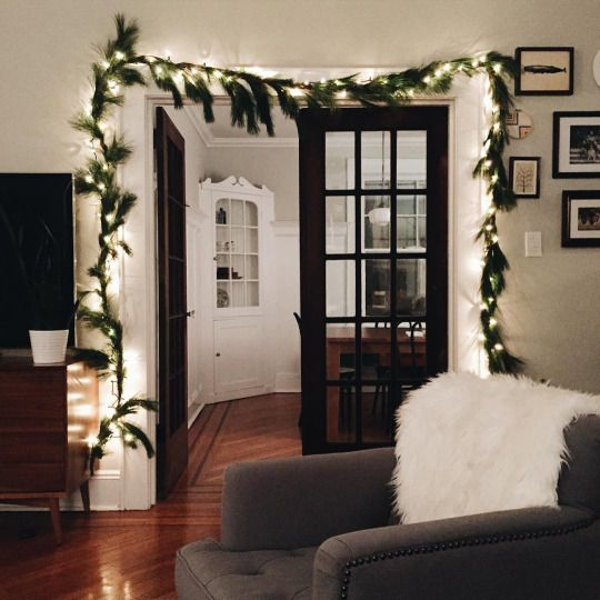 |1| Light Up The Space   Add pretty lights around the door of your living room and mix them with Christmas tree branches to give the room a holiday mood.