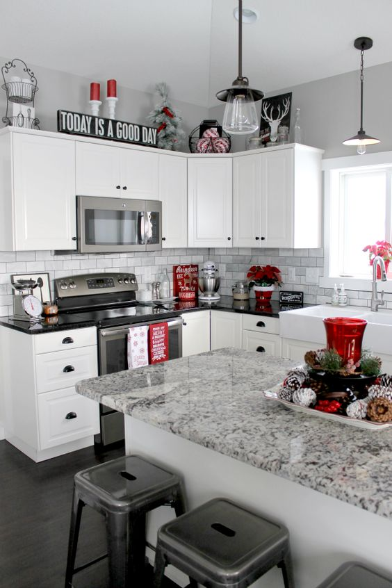 |8| Holiday Spirit In The Kitchen   Transform a minimal kitchen into a themed Christmas room by adding some red deco objects like flowers, candles and other cute decorations that will make you feel festive.