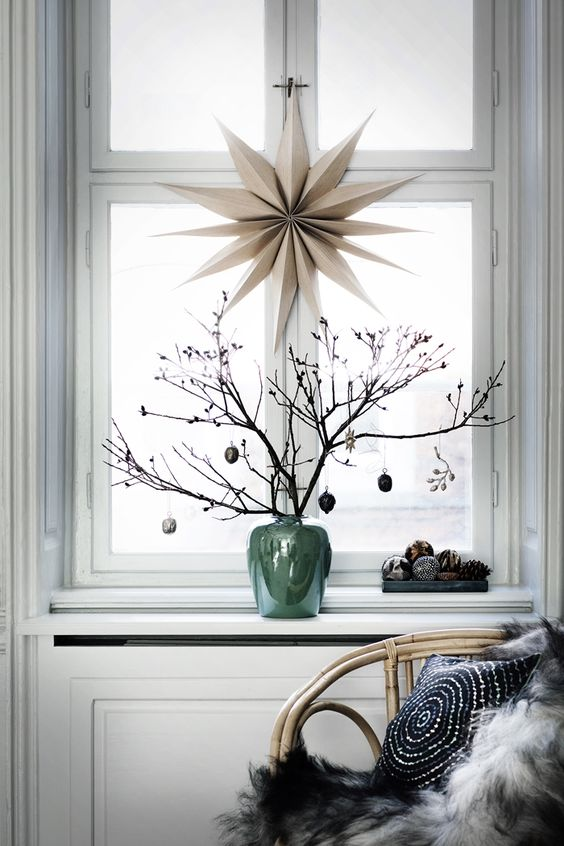 |10| The Chic Corner   This lovely Scandinavian deco will make your home really dreamy. Hang a big star on a window and add cute branches in a vase. Don't forget to decorate your home with pine cones and add a furry rug on a pretty chair.
