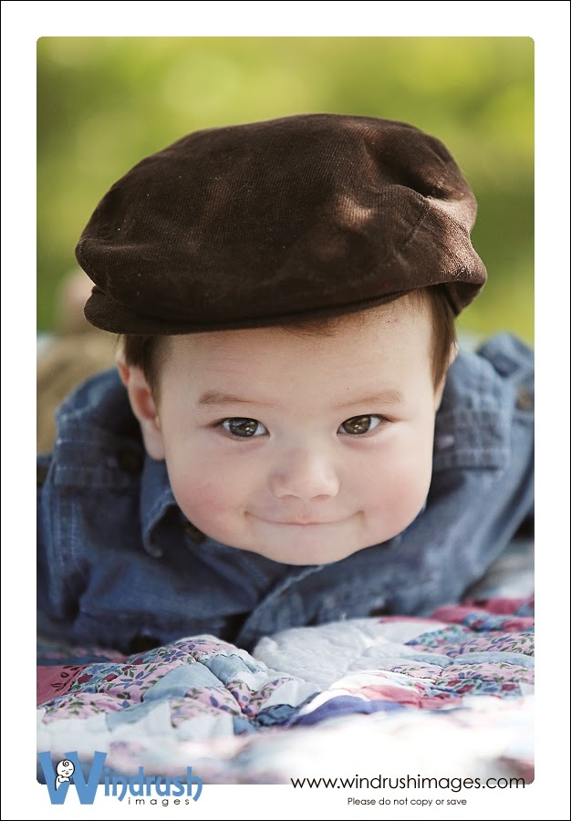 6 month old baby boy photographed in Calgary park wearing brown hat on quilt with gorgeous eyes
