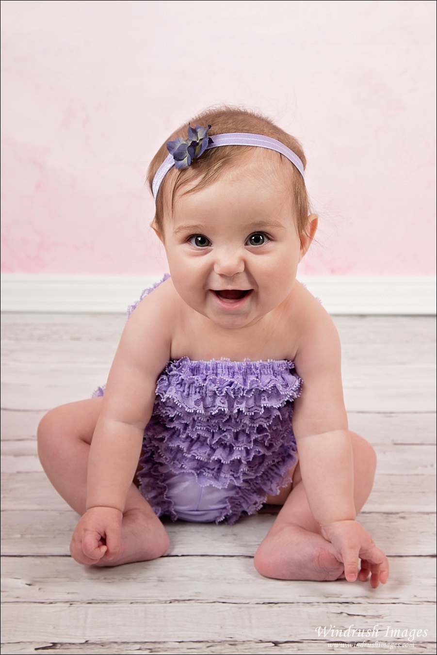 Smiling baby girl photo sitting for 6 month photo shoot in Calgary