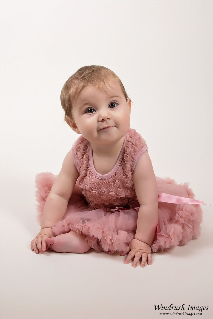 Sitting baby girl in pink princess dress for Easter themed pictures