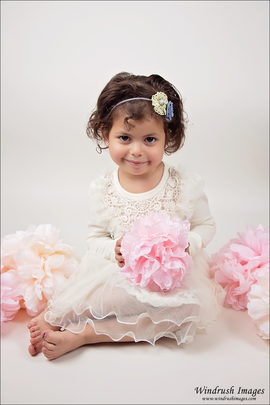 Spring kids photography session of little girl posed with pink white and peach florals in Calgary studio