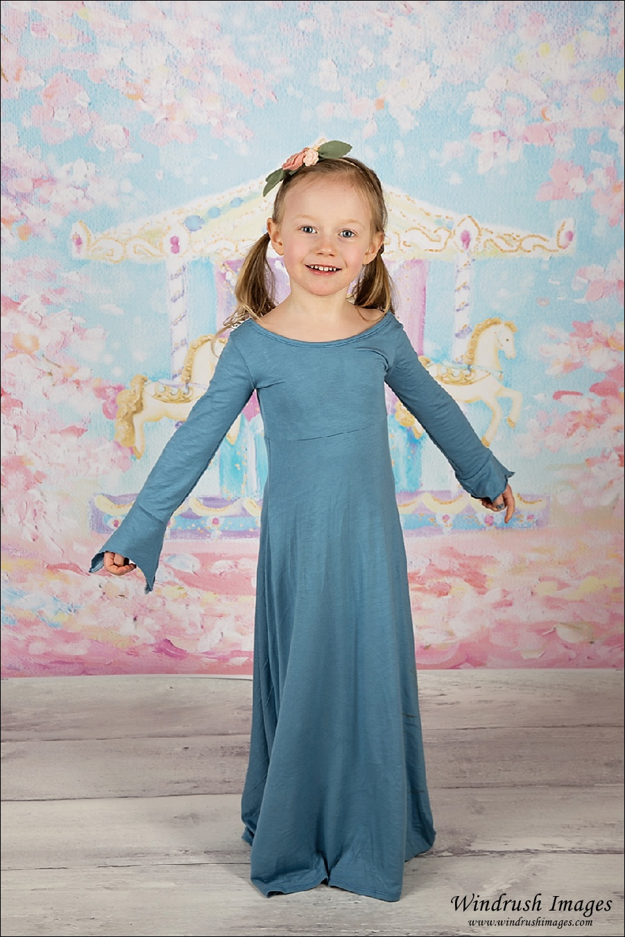 Little girl twirling in blue dress with carousel background for spring mini pictures in Calgary studio