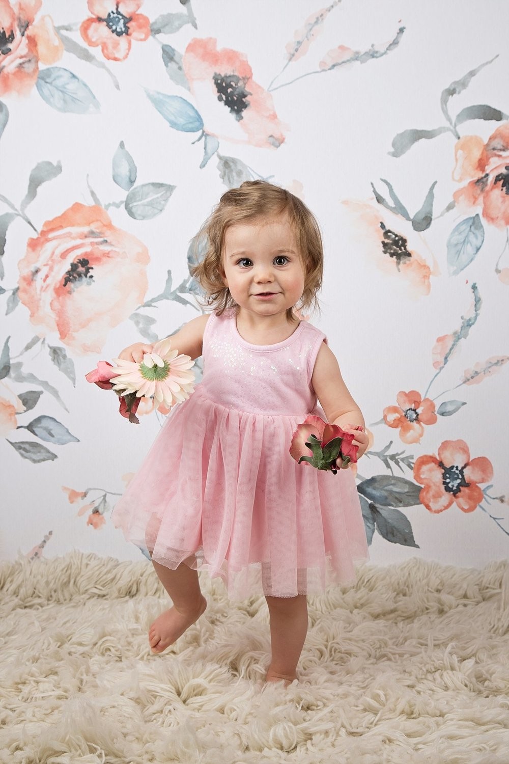 Adorable little girl in pink dress at spring photo shoot holding flowers with a floral background in Calgary photography studio for affordable  kids photos