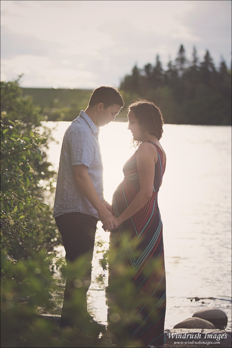Calgary maternity photography of gorgeous couple at sunset by the Bow River at Bowness Park