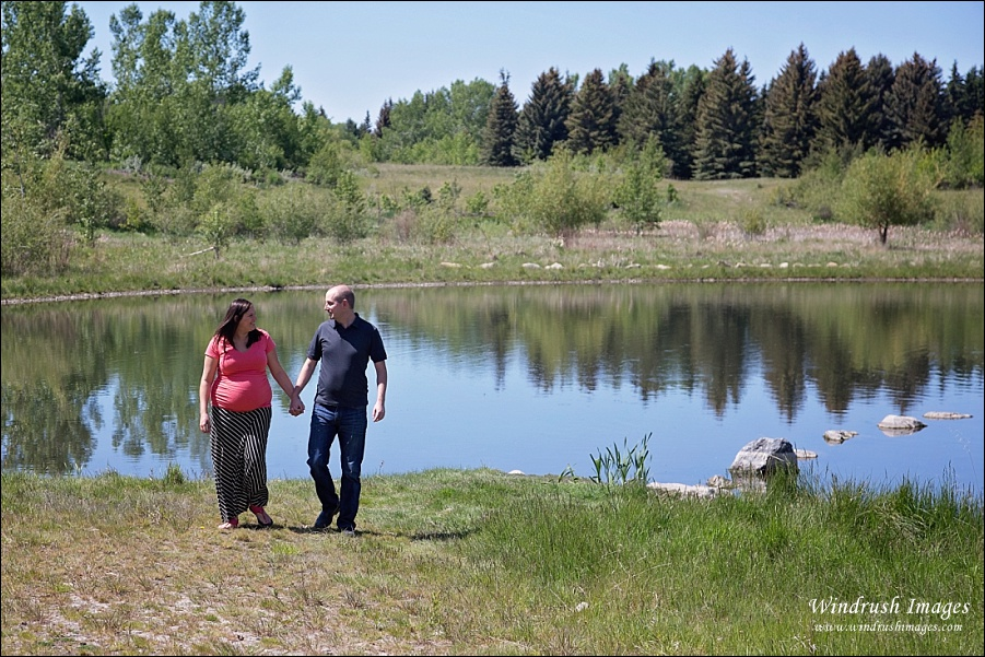 Calgary maternity photo shoot in North Glenmore Park with pregnant couple holding hands walking by scenic pond