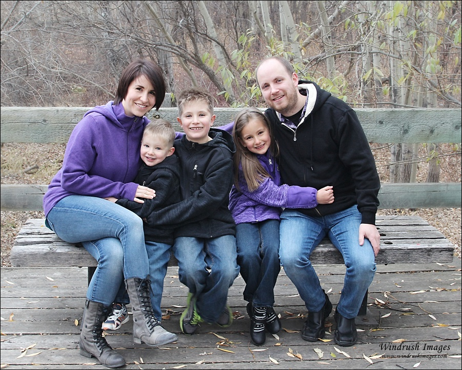 Picture of family of five sitting on a bench in late fall in Silver Springs Ravine in Calgary Alberta