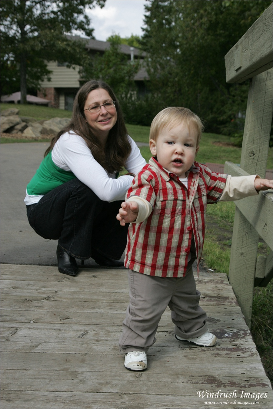 Mom lovingly watching one year old child walk on wooden bridge during Calgary family photo shoot