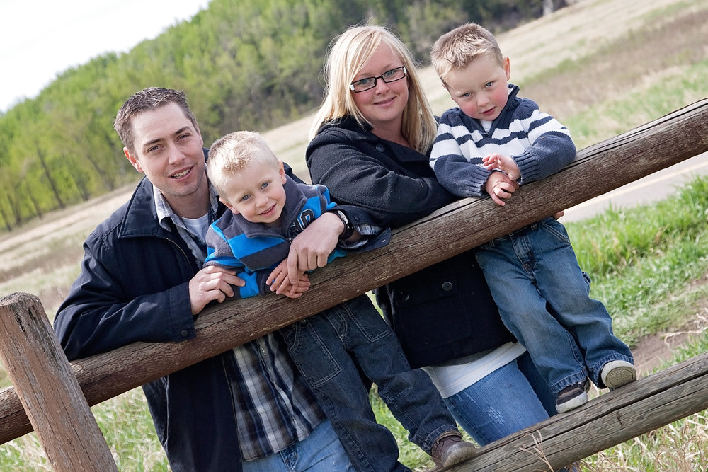Rustic family photography in Fish Creek Park in Calgary leaning on an old wood fence