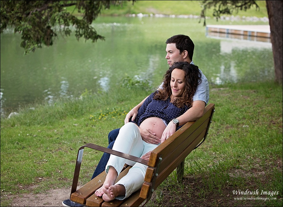 Maternity-photos-in-Calgary-of-lovely-couple-relaxing-on-a-bench-at-Bowness-Park-lagoon.jpg