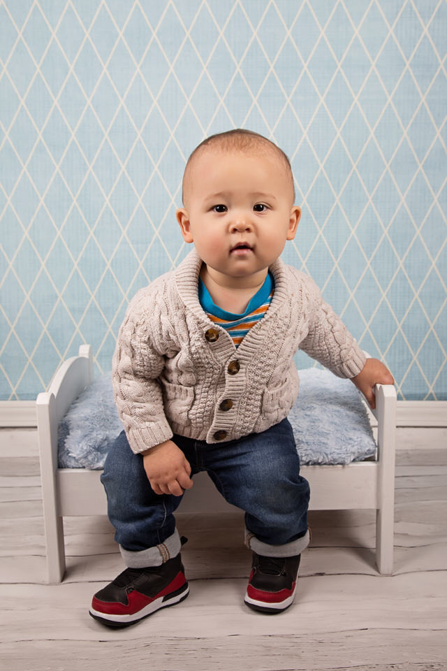 One-year-old-boy-at-Calgary-photography-session-sitting-on-bed-with-checkered-blue-background