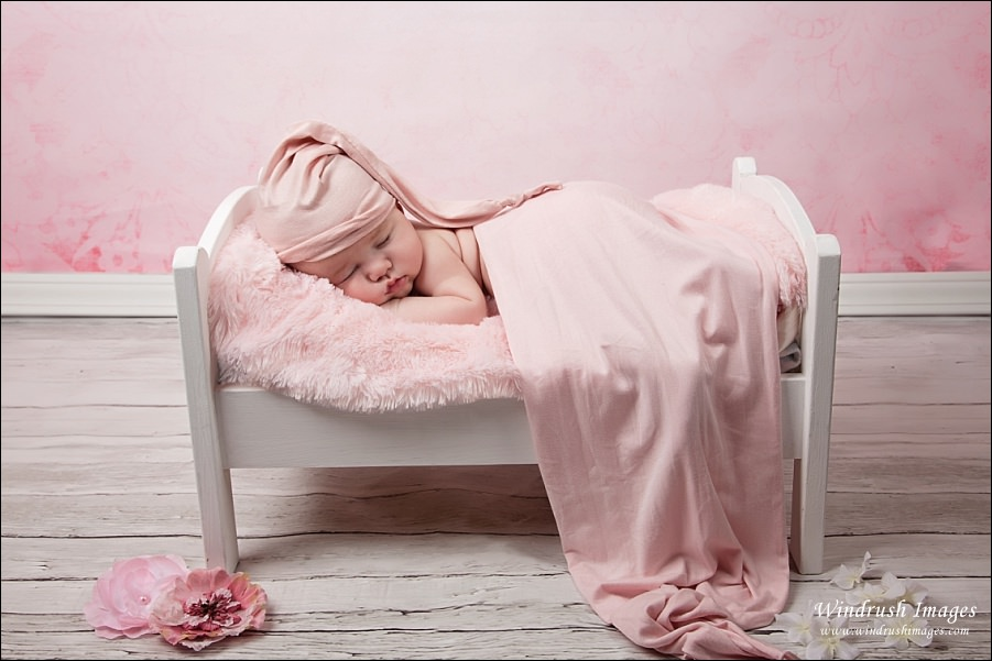 newborn-photographer-Calgary-baby-sleeping-on-pink-bed.jpg