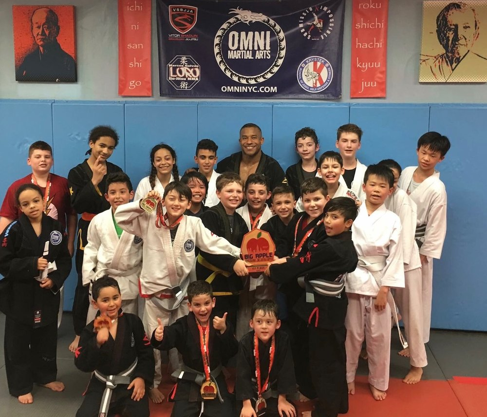 The Omni Kids Brazilian Jiu Jitsu Team shows off hardware from the 2017 Big Apple Tournament, where they won the trophy for best overall team along with a ton of individual medals!