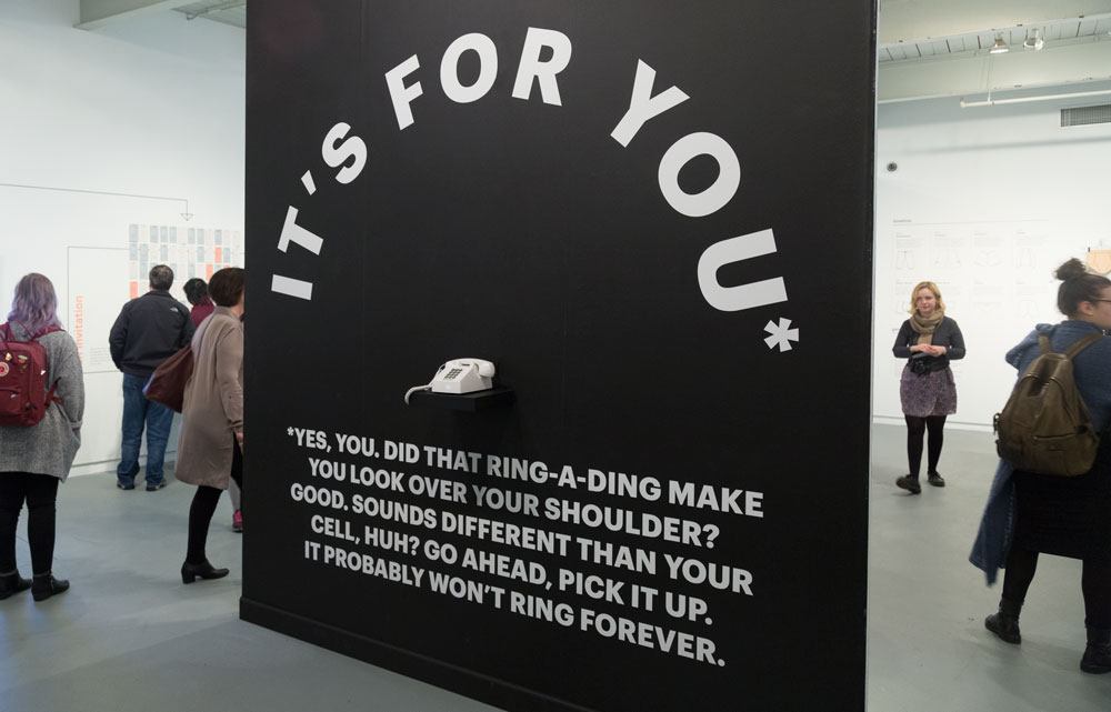 Side two of the instillation was a matte black wall with white vinyl. The visual language referred back to the paper towels on the opposite side, while acting as a strong counterpoint to the white tile. The phone sitting under the arched message was programed to ring randomly to deliver a message to whomever answered the call.
