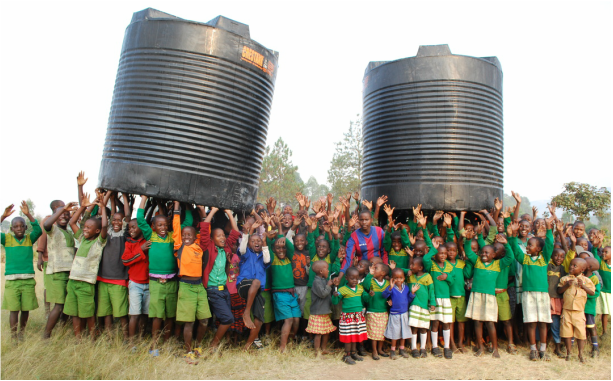 (Photo: students in Uganda receiving rainwater harvesting tanks from Old Westminster Winery)