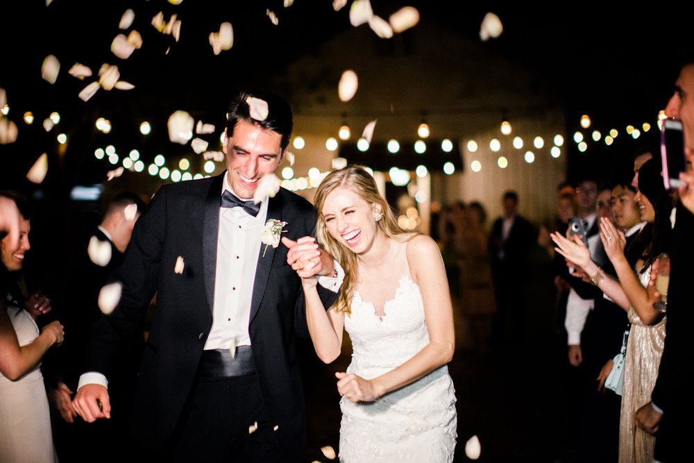 White rose petals thrown as the couple exits in their classic porsche  by Top Texas Wedding Photographer Hannah Mayson