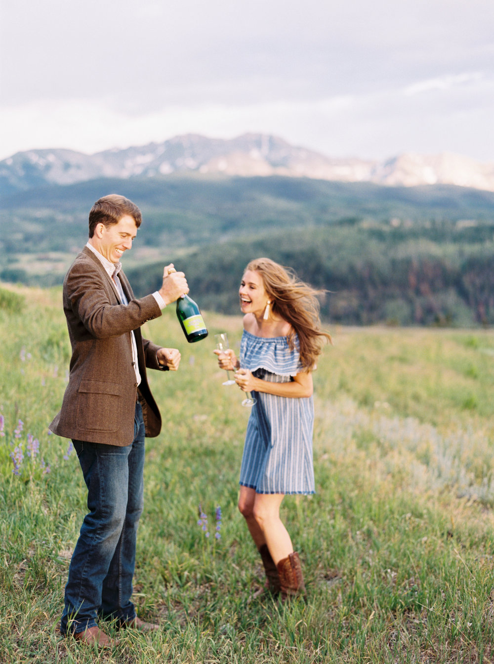 Bride and Groom pop Champagne after their Telluride engagement session by Top Colorado Wedding Photographer Hannah Mayson