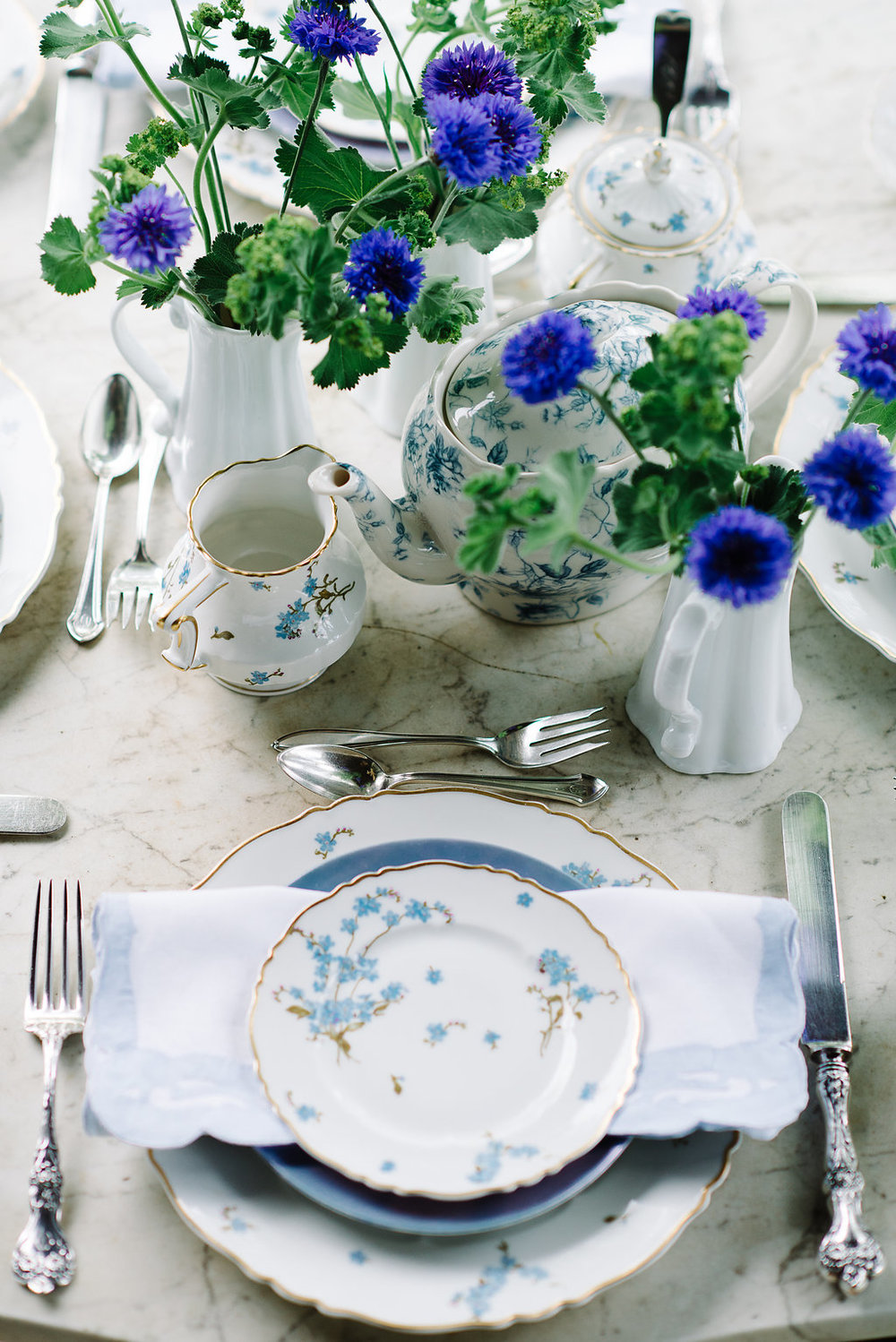 The marble table on the front porch was in the inspiration for this table.  Cindy's mother's china with a forget-me-not pattern was perfect paired with the bachelor buttons and ladies mantle.  Photo:  Norman Photo and Paper