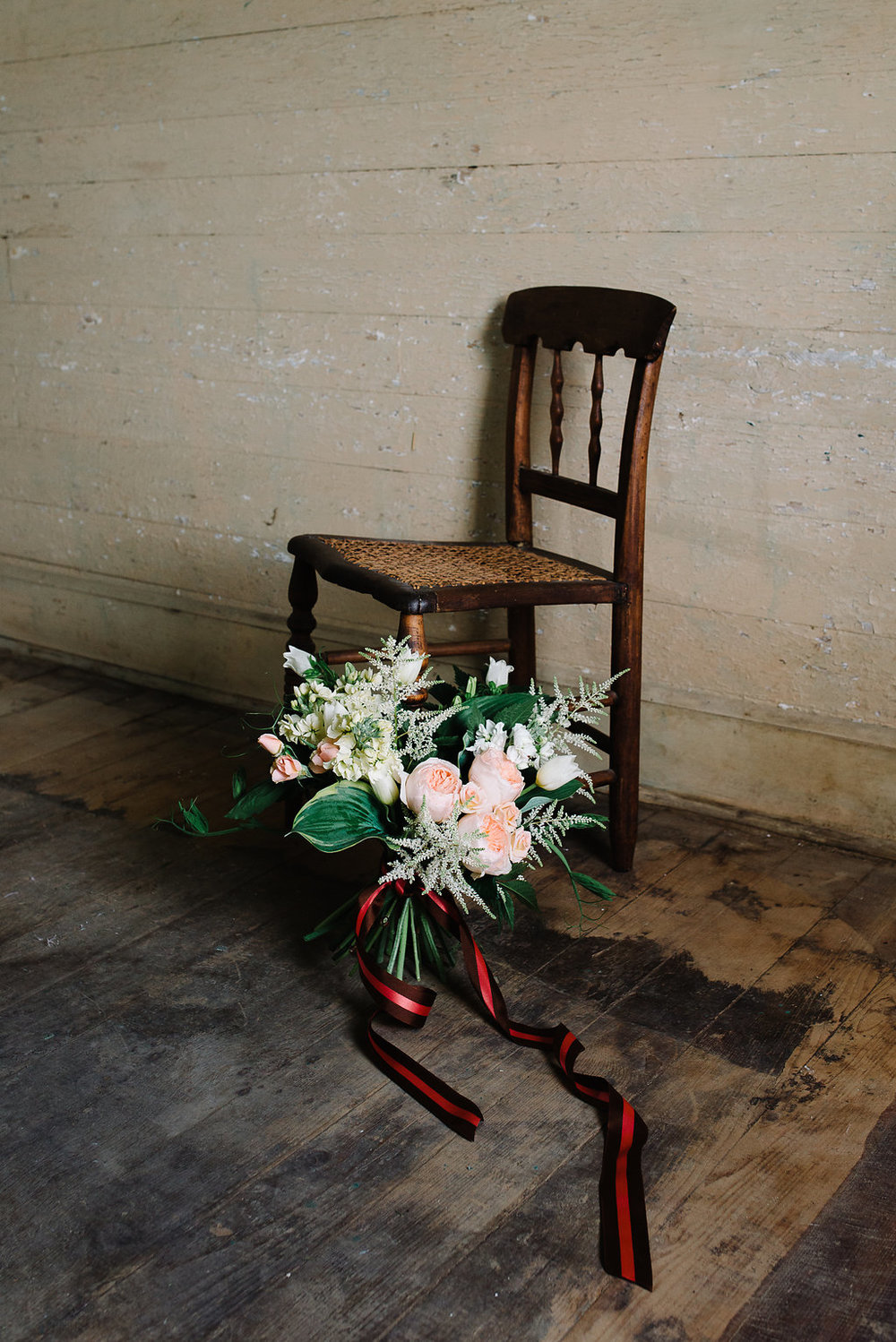 Bouquet with hosta, astilbe, garden roses, stock, tulip, campanula and pea shoots resting against a 19th century cane chair.  Photo by Norman Photo and Paper.